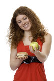 Hamburger or apple. Red haired teenager choose food Royalty Free Stock Photo