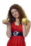 Hamburger or apple. Red haired teenager choose food Royalty Free Stock Photography