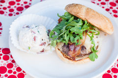 Hamburger with arugula, bacon and potato salad on the side Royalty Free Stock Photo