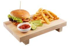 Hamburger auf einem Brett auf einem weißen Hintergrund mit Pommes-Frites, mit Soße und mit Gurke Lizenzfreies Stockbild