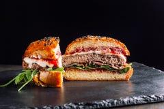 Hamburger auf einem schwarzen Schieferbrett Es wird zur Hälfte geschnitten Stockbild