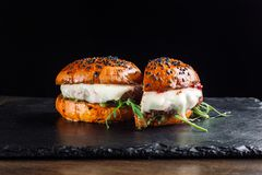 Hamburger auf einem schwarzen Schieferbrett Es wird zur Hälfte geschnitten Lizenzfreies Stockbild