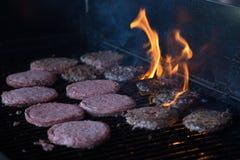 Hamburger auf Grill mit Flammen Lizenzfreie Stockfotos