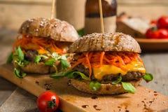 Hamburger avec de la viande et des légumes sur une table en bois Photos stock