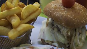 Hamburger avec des fritures sur la table en bois banque de vidéos