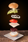 Hamburger avec des ingrédients de vol placés sur les planches en bois Image libre de droits
