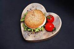 Hamburger avec des tomates sur le conseil en bois de forme de coeur Au-dessus du fond noir avec la pâte de copie Vue supérieure Images stock