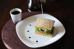 Hamburger avec du boeuf et verts dans les tranches de pain sans levain Du plat blanc avec des baisses de sauce Café sur le fond Image stock