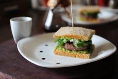 Hamburger avec du boeuf et verts dans les tranches de pain sans levain Du plat blanc avec des baisses de sauce Café sur le fond Photographie stock