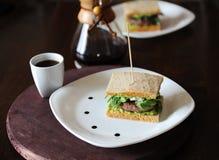Hamburger avec du boeuf et verts dans les tranches de pain sans levain Du plat blanc avec des baisses de sauce Café sur le fond Photos libres de droits