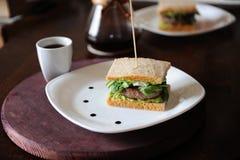 Hamburger avec du boeuf et verts dans les tranches de pain sans levain Du plat blanc avec des baisses de sauce Café sur le fond Image libre de droits