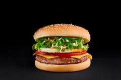 Hamburger avec la côtelette, fromage, tomate, laitue, omlette, d'isolement au fond noir photo stock