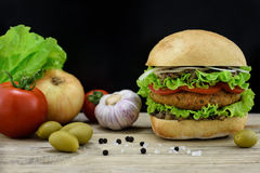 Hamburger avec les légumes frais sur le bureau en bois Photographie stock libre de droits