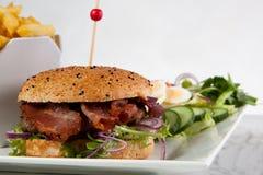 Hamburger bacon onion lettuce tomato french fries tartare sause stock photo