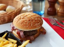 Hamburger with bacon on a white plate. stock image
