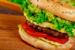Hamburger with beef, cheese and vegetables on wooden table. Closeup. Hamburger with beef with lettuce, cheese and vegetables on wooden table. Closeup stock photo