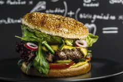 Hamburger on a black background in a studio. Hamburger on a black background in a studio with blurred out writings in a background royalty free stock images