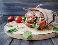 Hamburger with black bread and tomatoes on table Stock Photos