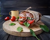 Hamburger with black bread and tomatoes on table Royalty Free Stock Photography