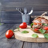 Hamburger with black bread and tomatoes on table Royalty Free Stock Photo
