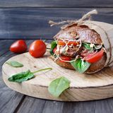 Hamburger with black bread and tomatoes on table Royalty Free Stock Image