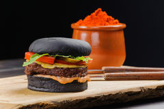 Hamburger. Black hamburger on a wooden board with knife and fork Stock Image