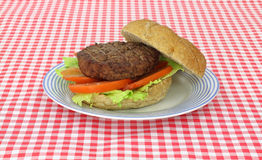 Hamburger on blue striped plate Royalty Free Stock Photography