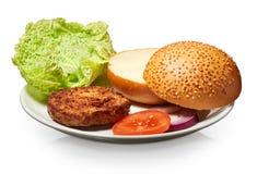 Hamburger, bun, onion, tomato,  and lettuce on white plate Royalty Free Stock Photo