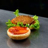 Hamburger caldo del falafel con lattuga, il pomodoro, la cipolla rossa e il tzatziki fotografia stock libera da diritti