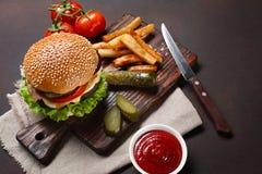 Hamburger casalingo con gli ingredienti manzo, pomodori, lattuga, formaggio, cipolla, cetrioli e patate fritte sul tagliere ed ar immagine stock