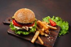 Hamburger casalingo con gli ingredienti manzo, pomodori, lattuga, formaggio, cipolla, cetrioli e patate fritte sul tagliere ed ar immagini stock