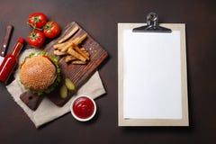 Hamburger casalingo con gli ingredienti manzo, pomodori, lattuga, formaggio, cipolla, cetrioli e patate fritte sul tagliere ed ar fotografia stock