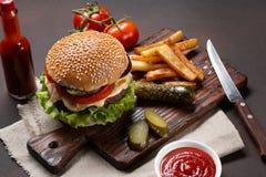 Hamburger casalingo con gli ingredienti manzo, pomodori, lattuga, formaggio, cipolla, cetrioli e patate fritte sul tagliere ed ar fotografie stock