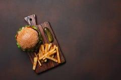 Hamburger casalingo con gli ingredienti manzo, pomodori, lattuga, formaggio, cipolla, cetrioli e patate fritte sul tagliere ed ar fotografia stock libera da diritti