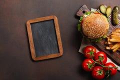Hamburger casalingo con gli ingredienti manzo, pomodori, lattuga, formaggio, cipolla, cetrioli e patate fritte sul tagliere ed ar immagini stock libere da diritti