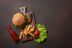 Hamburger casalingo con gli ingredienti manzo, pomodori, lattuga, formaggio, cipolla, cetrioli e patate fritte sul tagliere ed ar fotografie stock libere da diritti