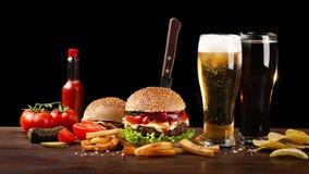 Hamburger casalingo con le patate fritte e due vetri di birra sulla tavola di legno Nell'hamburger ha attaccato un coltello immagini stock libere da diritti