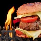 Hamburger casalingo del manzo del BBQ sulla griglia ardente calda Immagine Stock