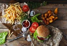 Hamburger casalingo, patate fritte, patate fritte, insieme degli alimenti a rapida preparazione Immagine Stock