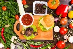 Hamburger cercado por vegetarianos e por coberturas frescos imagem de stock royalty free