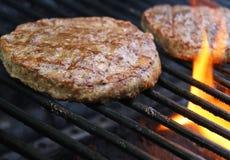 Hamburger che cucinano sopra le fiamme sulla griglia Immagini Stock