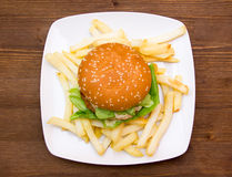 Hamburger with cheese and fries on wood from above Royalty Free Stock Photo