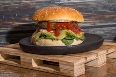 Hamburger with cheese and ketchup on black wooden plate stock images