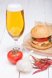 Hamburger cheese onions sauce tomatoes on paper and beer Royalty Free Stock Photo
