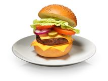 Hamburger with cheese, pickles, tomato, onions, lettuce on plate Stock Photos