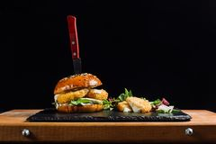 Hamburger with cheese sticks laid out on a black slate. Cheese beautifully flows. stock photo