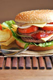 Hamburger with cheese, tomato, onion and lettuce Stock Photos