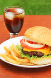 Hamburger. Cheesy burger served with a side of fries and refreshing cola on ice Royalty Free Stock Photos