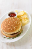 Hamburger with chips and sauce on white dish Royalty Free Stock Images