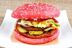 Hamburger classico con pane e gli ortaggi freschi rossi su un piatto bianco fotografia stock